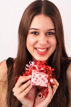 An excited young woman holds a small Valentines Day gift. photo