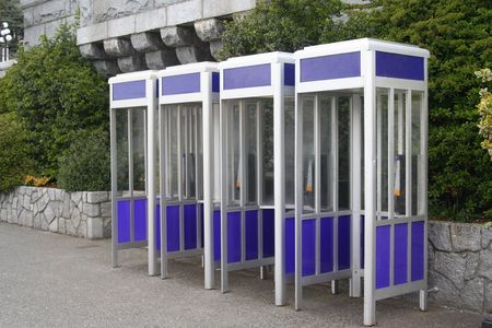 Blue Phone Booths.  A row of four identical phone booths. photo