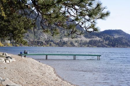 A mother and her small kids and dog sit on a distant dock enjoying the peacful morning view in this landscape shot of Lake Okanagan by Peachland, British Columbia, Canada. photo