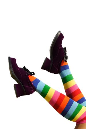suede: Happy Kicking Feet.  Geeky striped knee-hi socks and wickedly wonky, purple suede shoes on isolated girls legs.
