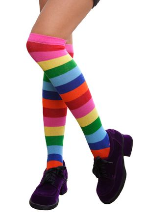 Pretty legs in a crazy combination of multi-colored striped knee-his & chunky purple suede shoes.  Isolated. Stock Photo