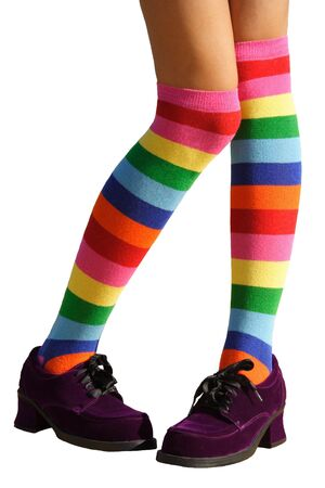 Awkward, bashful, schoolgirl legs in multicolored knee-his & chunky purple suede shoes.  Isolated. Stock Photo - 503804