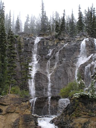 Beautiful waterfall surrounded by evergreens and new falling snow. near columbia icefields by jasper, alberta, canada. Stock Photo - 590676