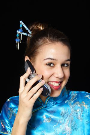 A happy, cell phone user.  Mixed race girl in oriental dress. photo