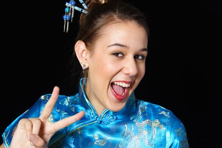 Mixed race girl in oriental dress flashes a big smile as she gives a peace sign. photo