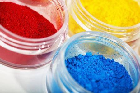 Macro of brilliantly hued pots of loose powdered eyeshadow.  Shallow depth of field.  Stock Photo