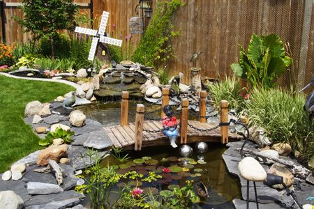 grasses: A beautifully designed water garden feature tied into a lovely perennial border, makes this backyard a wonderful place to relax and entertain in the summer. Stock Photo