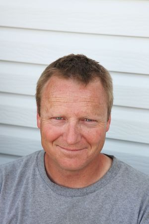 Eine durchschnittliche 40-jährige Mann auf seinem Deck entspannen. Er lächelt Ursache er benutzt Ihr Produkt!