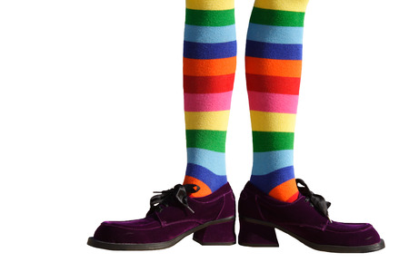 Wacky clown feet with crazy striped socks and oversized purple suede shoes!  Isolated.