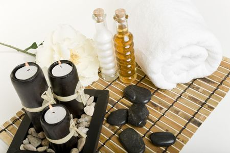 The candles are lit & massage stones, oils, & a towel are all laid out in preparation for a spa treatment.