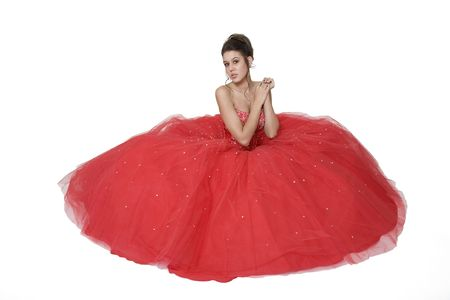updo: Teenage girl posing in her graduationprom gown against a white background.