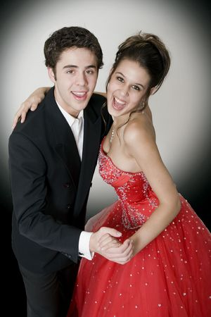 Boy & girl, in formal attire, dancing at their high school prom.
