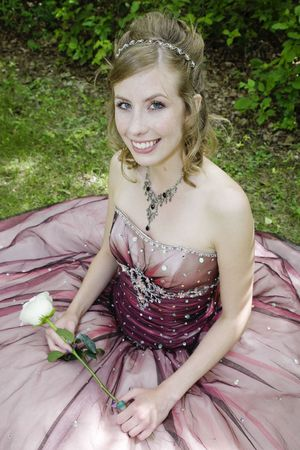prom queen: Fair, freckled beauty in elegant formal prom dress, holding a single sem white rose.  Dappled light. Stock Photo