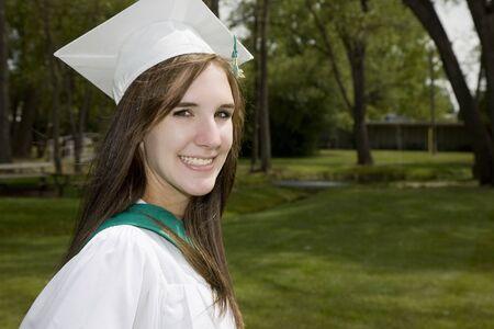 toga y birrete: Un feliz, sonriente ni�a de graduaci�n en la tapa y vestido. Foto de archivo