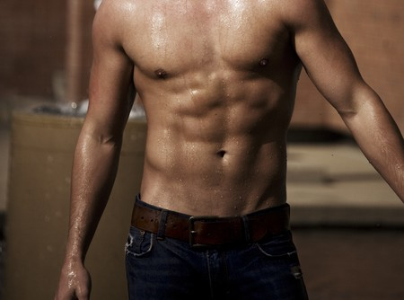 A built man's torso with water streaming off in the sunlight.