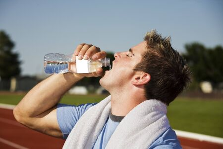 A thirsty athlete splashes some water down his throat after running a race. photo