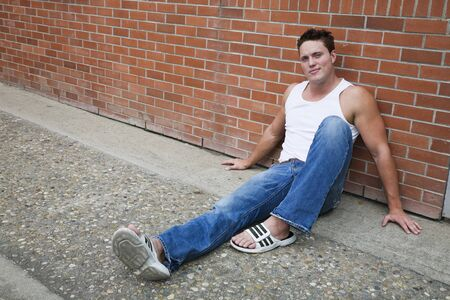 A young man sitting on a sidewalk , leaning against a brick wall. Reklamní fotografie