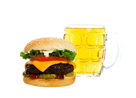 Juicy Angus beef burger topped with cheese, tomatoes & lettuce on a golden sesame seed bun along with a thirst quenching mug of beer.  Shot on white background.