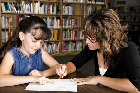 A little girl, in school learning from her teacher. 免版税图像