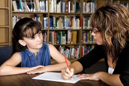 A young student listens intently to her teacher. Stock Photo