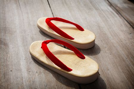 A pair of Japanese sandals on a wooden floor.