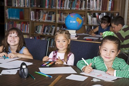 Elementary students in a school library doing art projects. Stock Photo - 4523734