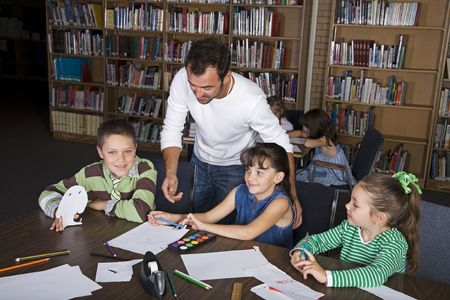 A teacher with his elementary students in the school library.