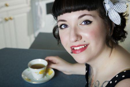 rockabilly: A rockabilly style girl enjoying tea. Stock Photo