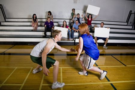 baloncesto chica: Dos jugadores de baloncesto frente a los equipos de gimnasia en la escuela, el hogar con los aficionados animando en el fondo.