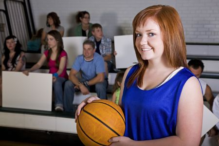 A female basketball player in the school gym, with her home fans in the background. photo