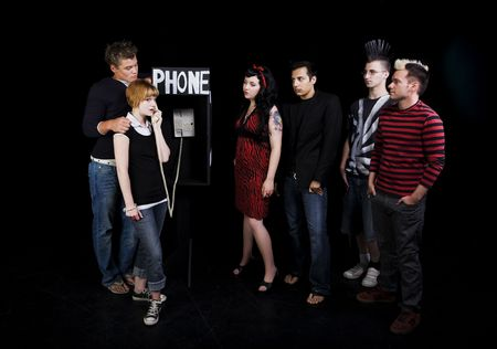 Six teenagers in a high school play.  A group of teenagers wait for their turn to use a public phone, while another girl hogs it. Stock Photo