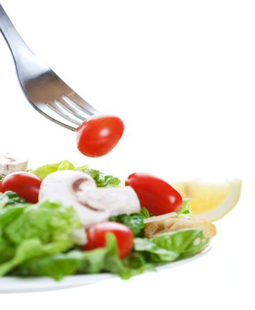 A cherry tomato on a fork above a freshly tossed salad.  Shot on white background.  Shallow depth of field. 스톡 콘텐츠