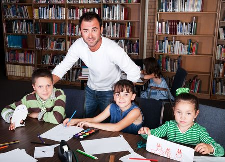 A teacher guides his students in an art class in the school library.