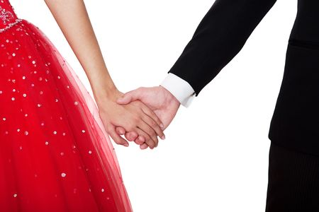 graduation suit: Boy & girl, in formal attire, holding hands against a white background.