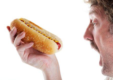 perro comiendo: Un hombre hambriento no puede esperar a dar un gran bocado de su delicioso perro caliente.