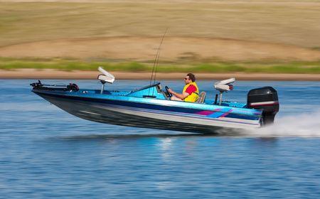 bateau de peche: Homme de conduire un bateau rapide avec la balance (motion blur) de fond. Banque d'images
