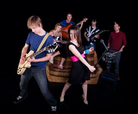 Six teens in a high school rock band practicing on a stage.
