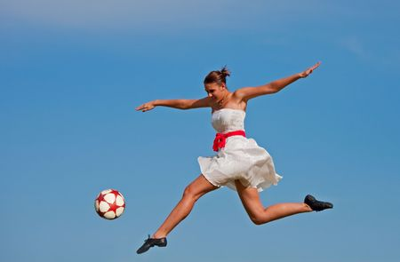 A beautiful girl kicking a soccer ball with the grace of a dancer. photo