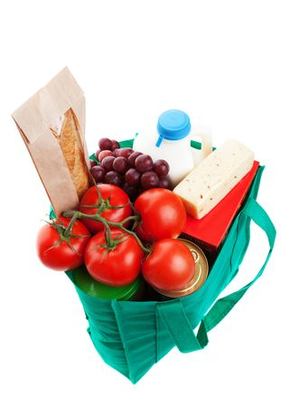 consumables: An eco-friendly, reusable, green cloth bag full of groceries.  Shot on white background.