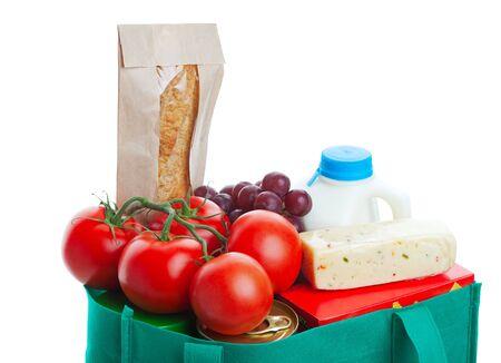 reusable: Closeup di generi alimentari in un eco-friendly, riutilizzabili, borsa di stoffa verde. Girato su sfondo bianco. Archivio Fotografico