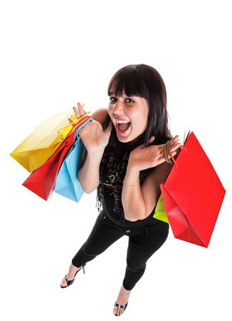 Smiling young woman, dressed Indie style, with shopping bags.  She is happy because of all the great sales!  Shot on white background with wide angle.