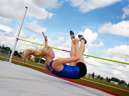 A young, athlete clearing the bar during a high jump event, in track and field. Фото со стока - 5362280