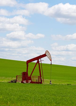 An oil well with the pump jack in action, against a grassy, green hill & cloudy blue sky.  Located in the province of Alberta, Canada. Foto de archivo