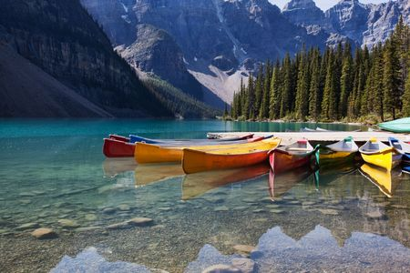 canada: Morning light on colorful canoes along the shore of Moraine Lake, Banff National Park, Alberta, Canada.