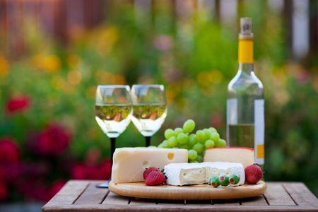 vinos y quesos: Una fiesta jard�n vino y queso para dos.  Poco profunda de la profundidad de campo.