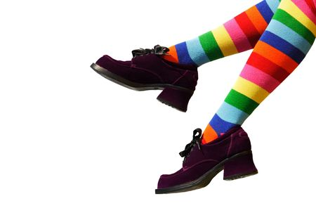 suede: Striped knee-hi socks and wickedly wonky, purple suede shoes on isolated girls legs.