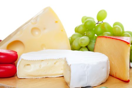A variety of  cheeses served complimented with green grapes.   Shallow depth of field.