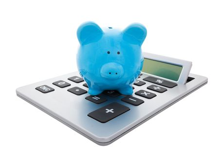 A blue piggy bank sitting on a large calculator.  Conceptual savings.  Stock Photo