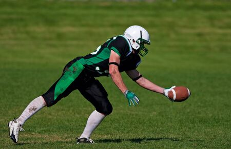 receiver: A young, football player about to catch the ball. Stock Photo