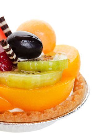 A decadent fruit tart, piled high with fresh fruit, and garnished with two delicate spikes of rolled white and milk chocolate.  Shot on white background with shallow depth of field. photo
